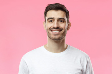 Close up portrait of smiling handsome man in white t-shirt isolated on pink background