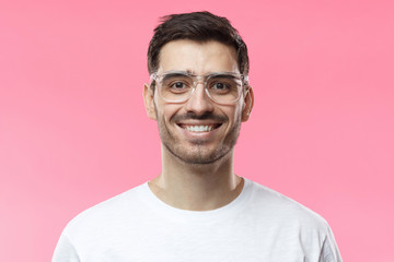 Close up shot of smiling attractive man in white t-shirt and trendy trasparent eyeglasses isolated on pink background