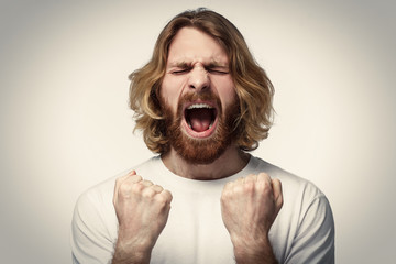 Closeup portrait of screaming with closed eyes crazy young man, raised both fist, isolated on gray background