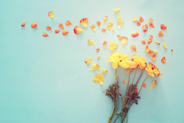 Image of delicate pastel orange and yellow beautiful flowers with petals arrangement over white wooden background. Flat lay, top view.