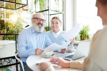 Senior couple with papers having talk with insurance or real estate agent in cafe
