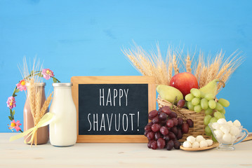image of dairy products and fruits over wooden table. Symbols of jewish holiday - Shavuot.