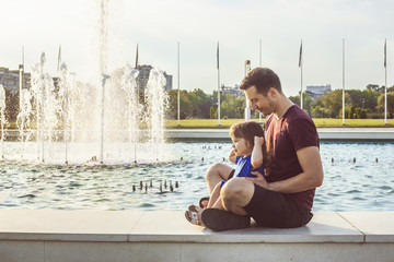 Father and daughter sitting by fountain