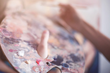 Young girl paints with oil paints. Close-up
