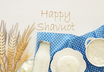 Top view image of dairy products over mint wooden background. Symbols of jewish holiday - Shavuot.