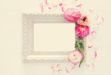 Image of delicate pastel pink beautiful flowers arrangement and empty vintage photo frame over white wooden background. Flat lay, top view. For photography mockup montage.