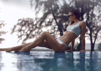 Beautiful girl in a silver swimsuit enjoys relaxing in the pool