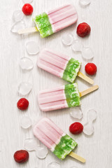 Pink green ice cream on a stick on a white wooden background. Strawberry and kiwi ice cream.