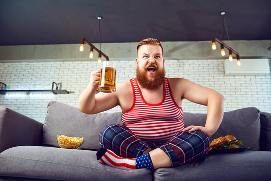 Thick funny man eating a burger sitting on the couch, watching TV at home against the background of the American flag.
