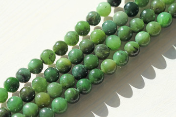 Natural green jade nephrite mineral stones beads. Green and grassy natural background made of round stone beads
