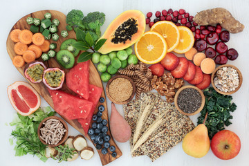 High fibre health food concept with multi seed crackers, cereals, nuts, fruit, vegetables and herbs. Foods high in omega 3 fatty acids, antioxidants, anthocynins and vitamins. Rustic background.