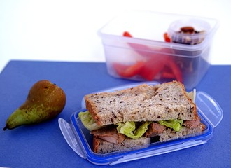 Lunch box for the student. Sandwich of corn bread with baked turkey and crispy lettuce leaves, pear, nut mix, sweet pepper