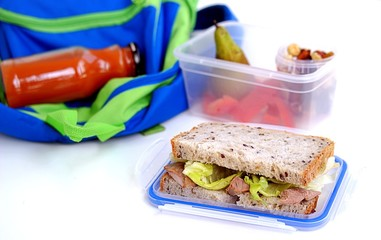 The concept of school food. Lunch box for the student. Sandwich of corn bread with baked turkey and crispy lettuce leaves, pear, nut mix, sweet pepper, carrot juice