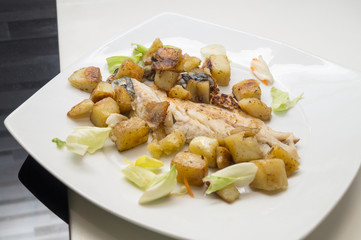 sea bass in the dish with potatoes and salad