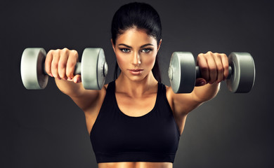 Beautiful fitness woman with  lifting dumbbells . Sporty girl showing her well trained body .  Well-developed muscles by strength training . Fitness, Sport and Beauty