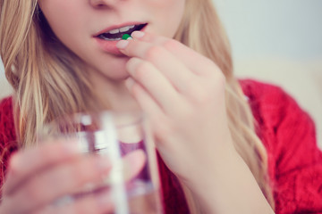 Young beautiful girl or woman take a pill or tablet with a glass of water at home.