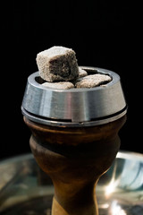 Hookah bowl with coals and smoke on black background