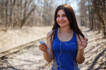 Young fit woman choosing music for outdoor training