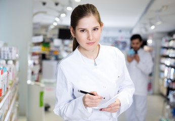 pharmacist  carefully keeps a re-inventory of medicines