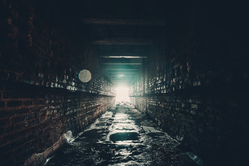 Dark brick wet tunnel or abandoned underground industrial corridor with light in the end