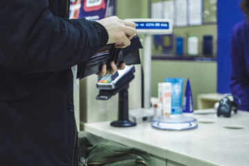 close up person paying cash in the store with wallet