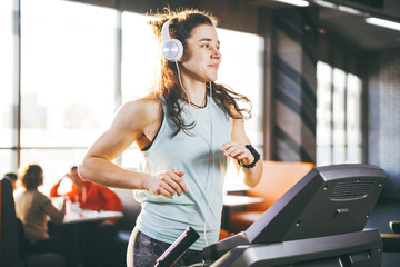 Theme is sport and music. A beautiful inflated woman runs in the gym on a treadmill. On her head are big white headphones, the girl listens to music during a cardio workout for weight loss