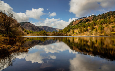 Irish Landscape - Blue sky with clouds and mountains reflecting in the calm water of the Lower Lake at the heart of the Glendalough Valley in Wicklow National Park in Ireland.
