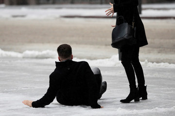 A man slips on icy snow covered sidewalk as freezing rain falls in Toronto