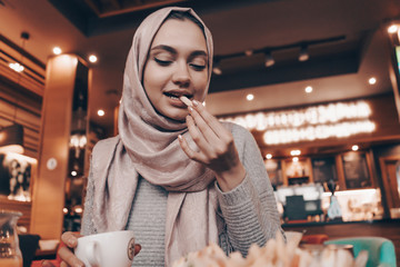 nice beautiful Arab girl with a headscarf, wearing a hijab, having lunch in a cafe