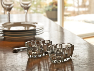 Silverware utensil holders with forks and spoons and dinnerware on wood table