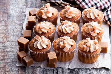 Toffee  cupcakes with white cream on wooden table