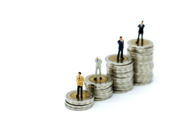 Miniature people : Businessman standing with wooden bar chart icon and stack of coins,Business Vision Concept.