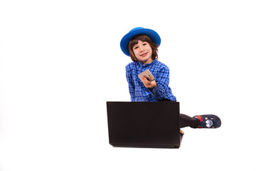 Cheerful little executive boy with smart phone and laptop