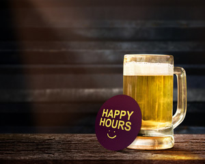 Happy Hours Promotional Concept. Glass of Beer on the Wooden Table in Bar with Paper Note and Word