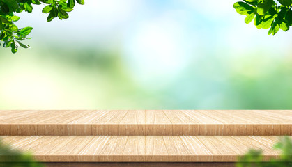 Empty step plank wood table top with blur tree in park with bokeh light background and leaves foreground,Mock up template for display of your design,Banner for advertise of product,panorama view