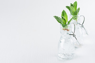 Two transparent bottles with fresh green mint sprigs on white wood background. Spring interior, copy space.