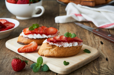 Bruschetta with ricotta cheese and strawberries on a wooden board