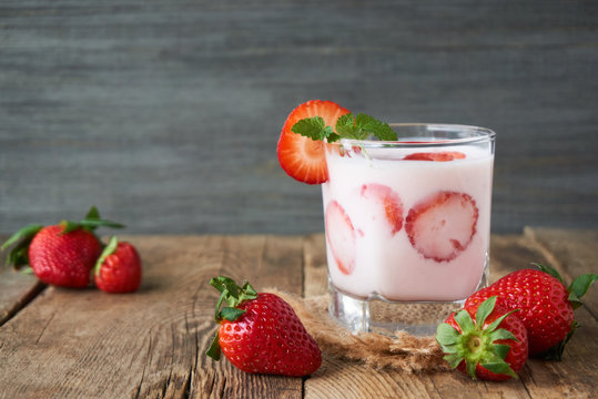 Strawberry yogurt in a glass on a wooden table