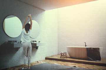 White tub in a white bathroom corner, woman