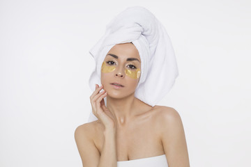 Patches under the eyes. Skin care under the eyes. Beautiful young smiling woman with a towel on her head, a girl after a shower. Beauty and spa. Face and body care. Cosmetology.