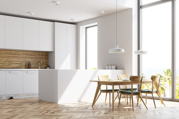 White and wooden kitchen with a table, side view