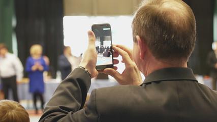 Bald man shooting a smartphone award at the tournament