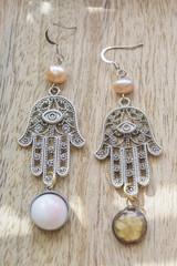 romantic earrings on wooden background