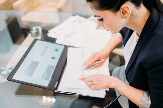 business analyst studying report papers with graphic results of company activity. information processing and data analysis concept. young professional woman at work