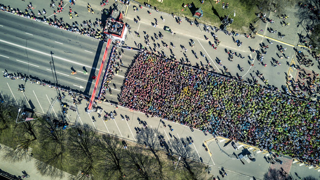 Aerial view from drone on crowd of people who is starting their run on marathon event. Funny shadows on asphalt.