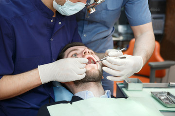 A dentist with an assistant treats a patient's teeth.