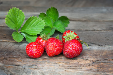 Ripe sweet strawberry with green leaves on wooden table. Closeup food photo.