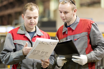 Industrial manufacturing workers reading engineering drawing in factory workshop, consulting and solution