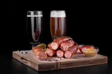 beer snacks, Original sausage with a sauce with two glasses of beer.