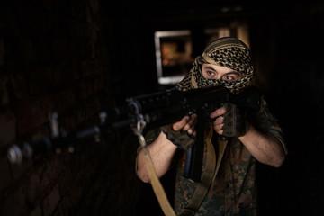 Arab soldier aiming with Kalashnikov AK-47 assault rifle